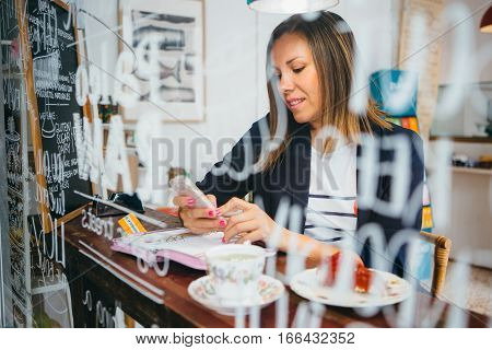 Portrait of smiling brunette chatting over phone in cafe.From behind window