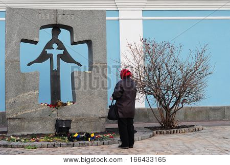KIEV UKRAINE - January  24 2017: The memorial to the victims of Holodomor 1932 -1933 years on Mykhailivska Square in Kyiv. A memorial dedicated to the Terror-Famine in Ukraine. Praying woman.
