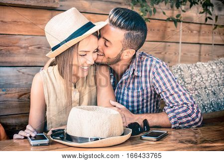 Young fashion couple of lovers at beginning of love story - Handsome man whispers sexy kisses in pretty woman ear - Relationship love concept with boyfriend and girlfriend together - Warm retro filter