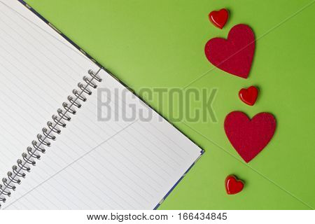 Open notebook and red hearts on greenery background. Valentines day concept. Top view. Flat lay. Copy space for text