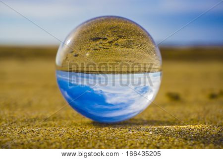 Glass ball lying in the sand against the background of the sea waves and sky with clouds.