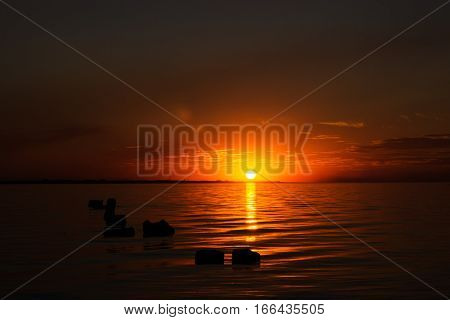 bright yellow golden sunset with reflection in sea surface above the sea surface with piles sticking out of the water