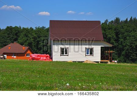 Building beautiful house with siding walls and roofing with asphalt shingles or bitumen tiles near forest in cozy cottage town