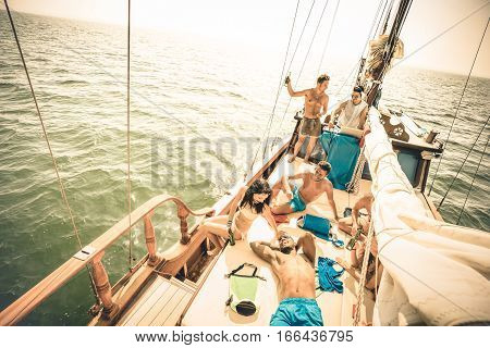 Happy multiracial friends having fun at sail boat trip party with dj set - Friendship concept with young multi racial people on sailboat - Travel lifestyle on exclusive location - Warm retro filter