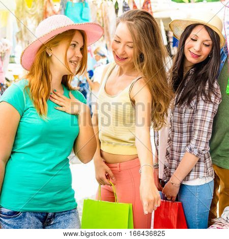 Young beautiful women girlfriends at flea market looking for fashion cloth - Friendship concept with best female friends having fun and shopping in old town - Vivid saturated color tones filter
