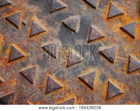 Close-up of part of a rusted manhole cover with triangle pattern