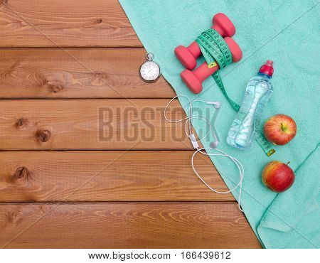 Bottle with towel dumbbells and skipping rope on wooden table background. Fitness lifestyle concept.