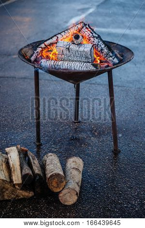 Photography of a stainless steel barbecue grill and firewoods