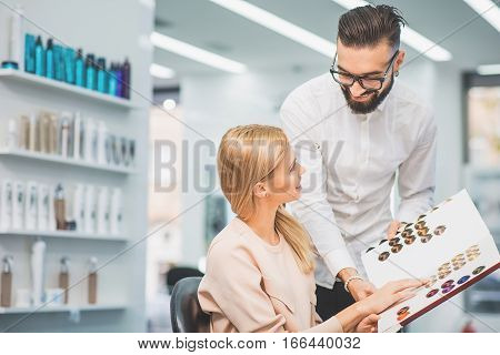 Professional stylist is talking to a client. The woman is choosing hair color