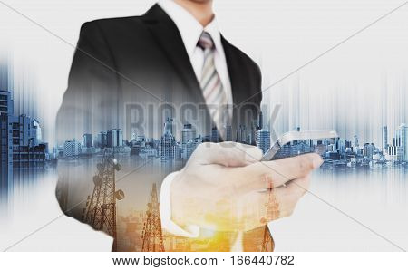 Double exposure businessman holding smartphone with telecommunication towers and modern buildings in sunrise, business network communication technology