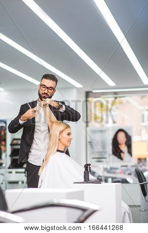 Focus on stylist and client. The man is standing and cutting long blond hair