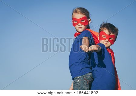 Happy little children playing superhero. Kids having fun outdoors. Concept of power.