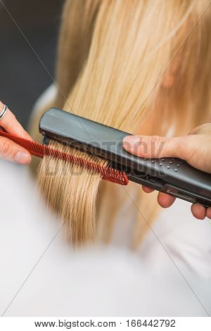 Close-up of a man working with a client. He is straightening long blond hair. Focus on iron