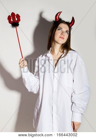 young girl in a man's white shirt with red horns holding a trident and looks like pretty Devil.