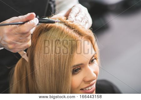 Close-up of a woman getting new haircut. She is smiling. The hairdresser in gloves is dying her hair