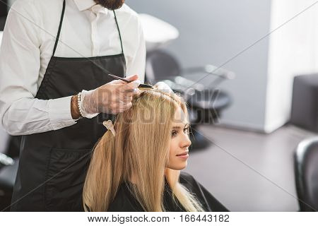 Calm girl with long blond hair is waiting in a salon. The stylist is dying her hair