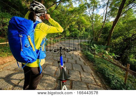 young woman cyclist adjust the helmet belt before riding mountain bike on forest trail
