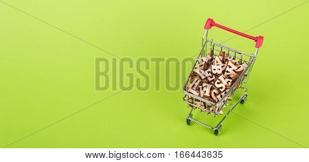 Shopping basket with letters of the alphabet made of wood on a green background