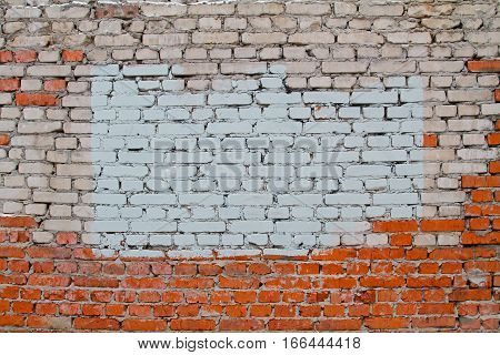 Background of old brick wall of white and red bricks with painted splotch