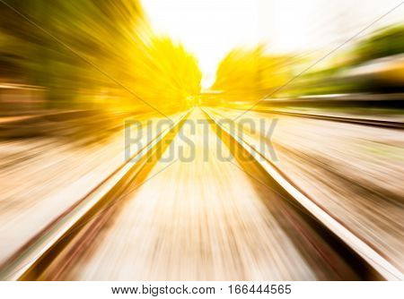 motion blur of railway moving forward by train among warm sunshine