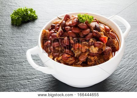 Beans with pork stewed in spicy tomato sauce with onion paprika beer bell and pink pepper. White soup bowl and fresh parsley on black stone.