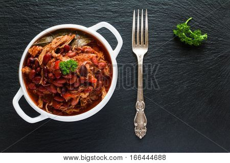 Beans with pork stewed in spicy tomato sauce with onion paprika beer bell and pink pepper. White soup bowl vintage fork and fresh parsley on black stone top view.