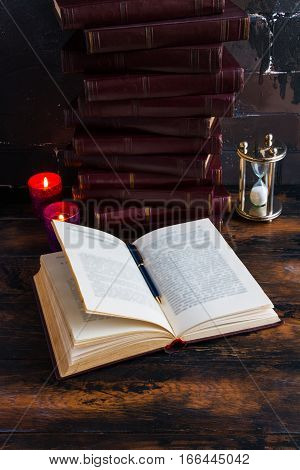 Old vintage books with red hard cover laying like a tower on a dark wooden table and one open book. Burning candle flames and hourglass.
