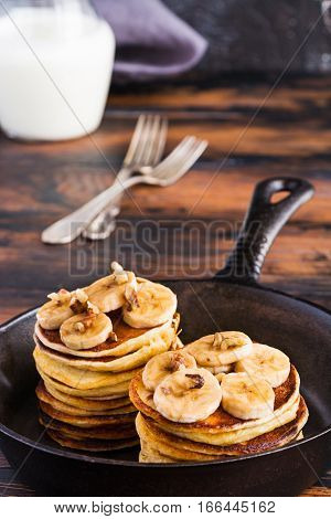 Stack of homemade pancakes with banana maple syrup and walnuts in black cast iron skillet. Vintage forks glass jar with milk wooden rustic table.