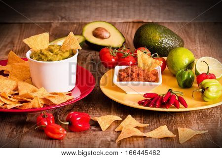 Guacamole and nacho chips on wooden table.