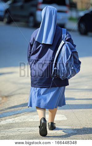 Nun With Blue Dress And Veil With A Backpack