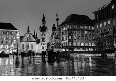 Munich, Germany. Marienplatz at night in Munich, Germany with old town hall and other buildings - cafes, bars, shops and restaurants. Motion blurred people. Black and white