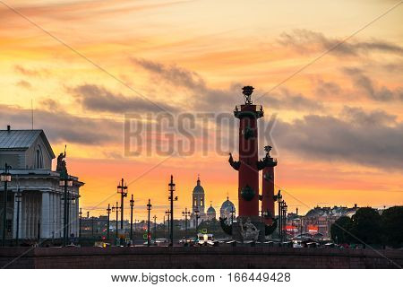 St Petersburg, Russia. Sunset over Strelka - Spit of Vasilyevsky Island with the Old Stock Exchange and Rostral Columns in Saint Petersburg, Russia