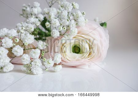 Closeup of wedding bouquet made of Persian buttercups, Ranunculus and white baby's breath Gypsophila flowers lying on the white table.