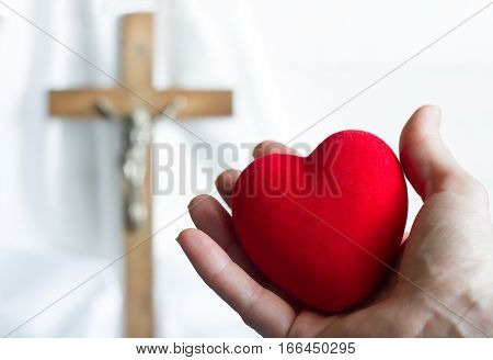 Giving heart to Jesus abstract concept with easter cross on a white background