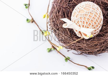 Spring easter egg in knitted bag in nest with easter decor. Selective focus.