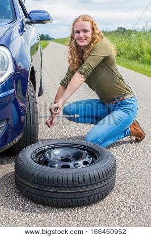 Young european woman changing car tire on country road