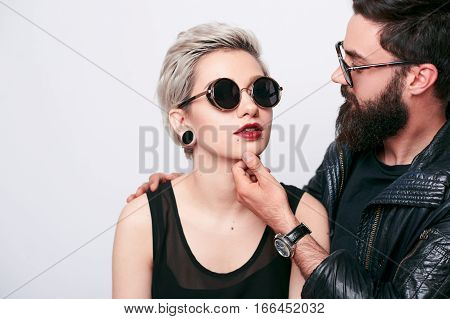 Romantic couple in love. Hipsters temptation. Young woman in stylish black retro sunglasses and bearded masculine man embracing and playing