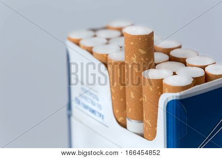 Open pack of cigarettes with a one protruding cigarette closeup