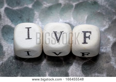 the word ivf (in vitro fertization) lined with wooden blocks on a metal forged textural background.