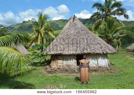 Indigenous Fijian Man Dressed In Traditional Fijian Costume, Stand Outside His Bure