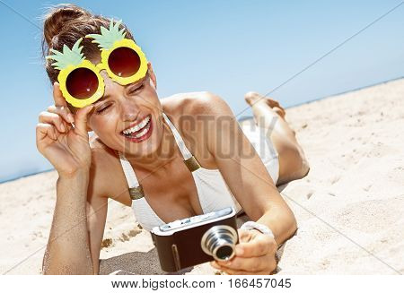 Woman In Pineapple Glasses Checking Photo At Sandy Beach