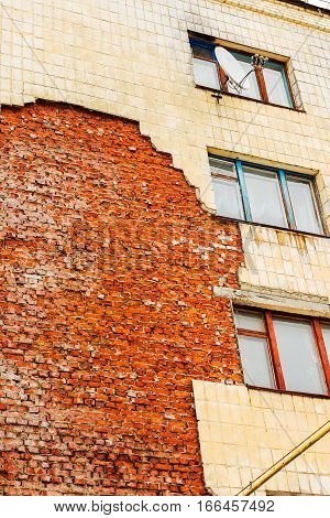 Old high-rise building with broken windows crumbling walls covered with cracks and scratches