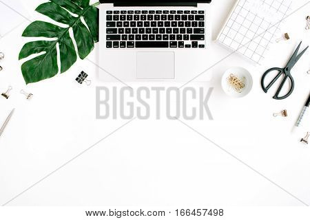 Home office workspace with laptop palm leaf notebook scissors and accessories. Flat lay top view