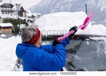 Older Woman Cleaning Car of Snow with Shovel. Transportation Winter and Vehicle Concept.