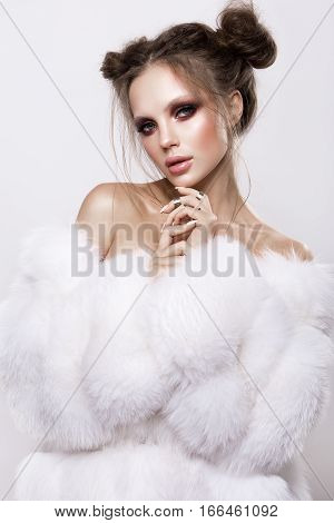 Beautifful european brunet woomen with gloss clean healfy skin, glooss shiny pastel pink lipstik and with trendy fashion hairstyle in white fluffy fur coat