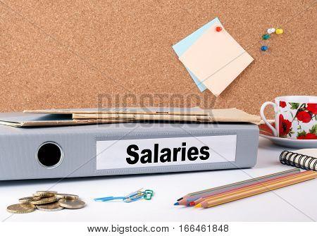 Salaries. Folder and a coffee mug on a white table.