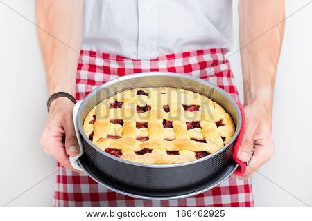 Man baked pie, freshly baked pie, fresh fruit dessert, chef holding baked pie