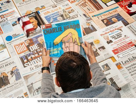 PARIS FRANCE - JAN 21 2017: Man holding Charlie Hebdo with Trump caricature above major international newspaper journalism featuring headlines with Donald Trump inauguration as the 45th President of the United States in Washington D.C