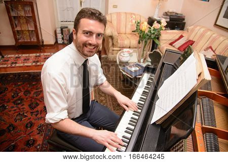 Cheerful music performer playing his piano at home