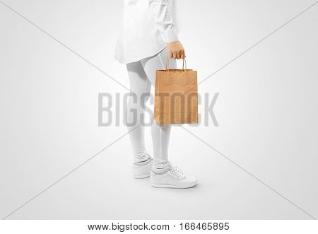Blank brown craft paper bag design mockup holding hand, clipping path. Woman hold kraft textured purchase pack mock up. Clear shop bagful branding template. Shopping carry package in persons arm.